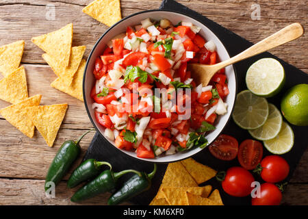 Homemade spicy pico de gallo close-up in a bowl and nachos on the table. Horizontal top view from above - Stock Photo