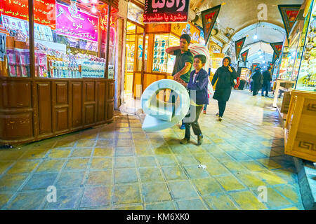 YAZD, IRAN - OCTOBER 17, 2017: Happy iranian family carries goods after the shopping in Bazaar, on October 17 in - Stock Photo