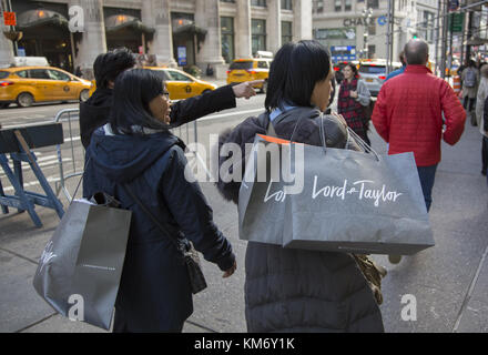 Holiday shoppers on the street in midtown Manhattan, New York City. - Stock Photo