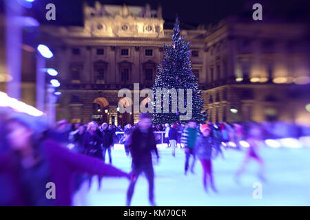 Ice skaters glide at night on the temporary ice rink at Somerset House in London during the Christmas month of December - Stock Photo