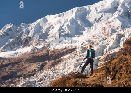Standing young woman with backpack on the mountain peak and looking on beautiful mountains and glacier at sunset. - Stock Photo