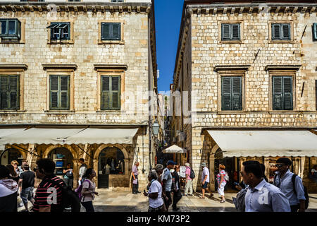 Tourists walk the stradun, main street in the historic walled city of Dubrovnik on a sunny, warm day on the Adriatic - Stock Photo