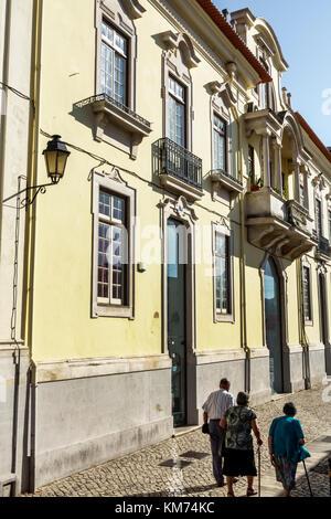 Coimbra Portugal historic center residential apartment building street alley woman man senior walking cane - Stock Photo