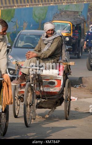 Punjabi man sits on his cycle rickshaw in Amritsar, India - Stock Photo