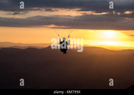 A paraglider silhouette flying against the sunset over Mt.Cucco (Umbria, Italy) - Stock Photo