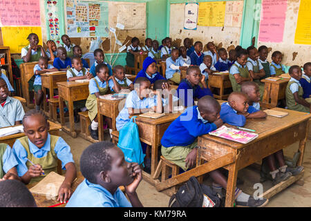 Secondary school children in uniform sat at desks listening to their teacher during class, Nairobi, Kenya - Stock Photo