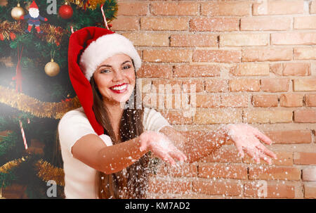 Smiling woman in santa hat with show in her hands. Merry Christmas and Happy New Year concept - Stock Photo