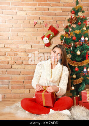 Pretty young woman sitting in decorated room with Christmas tree and presents under it. Merry Christmas and Happy - Stock Photo