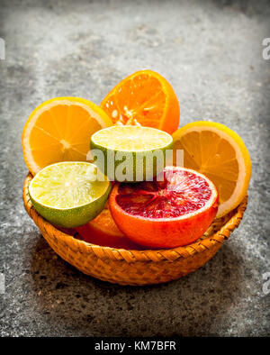Sliced citrus fruits in a basket. On rustic background . - Stock Photo