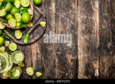 Fresh drink with lime slices. On wooden background. - Stock Photo