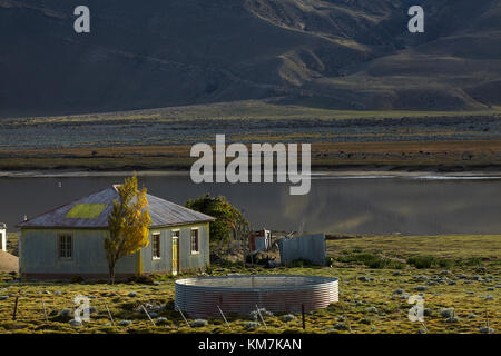 Old corrugated steel farmhouse and small lake near El Chalten, Patagonia, Argentina, South America - Stock Photo