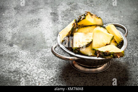 Pineapple in a bowl. On rustic background. - Stock Photo