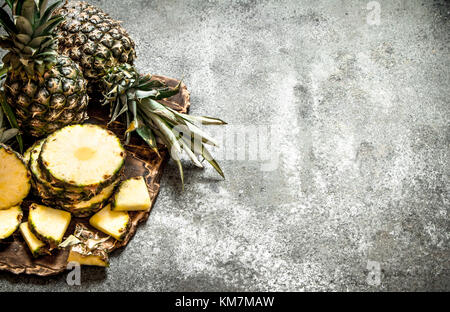 Ripe fresh pineapples. On the rustic background. - Stock Photo