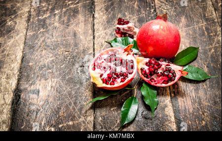 Ripe fresh pomegranates. On the wooden background. - Stock Photo