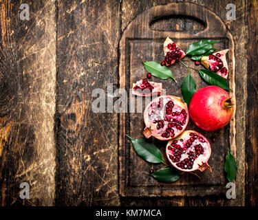 Ripe pomegranates on a cutting Board. On wooden background. - Stock Photo