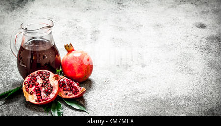 Fresh pomegranate juice in a glass jug. On rustic background. - Stock Photo