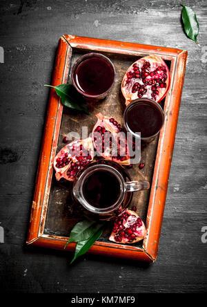The fresh juice of ripe pomegranate. The black chalckboard. - Stock Photo