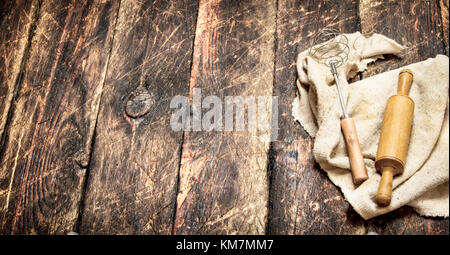 Serving background. Rolling pin and whisk on an old fabric. On a wooden table - Stock Photo