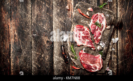 Raw meat background. Pieces of raw steak with spices and herbs. On wooden background. - Stock Photo