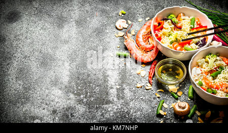Asian food. Chinese noodles with vegetables and shrimp. On an old rustic background . - Stock Photo