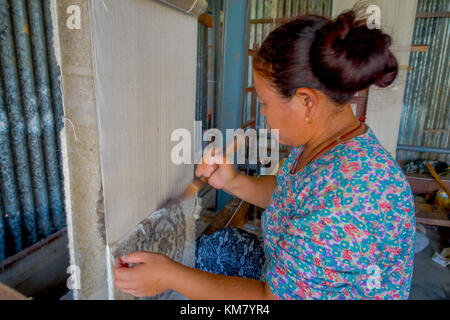 POKHARA, NEPAL - OCTOBER 06 2017: Close up of unidentified woman working on loom manufacturing wool shawl clothing - Stock Photo