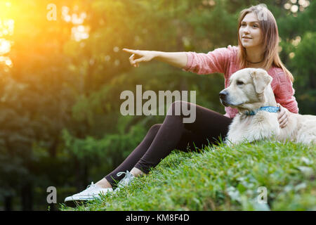 Photo of girl pointing forward next to dog on green lawn - Stock Photo