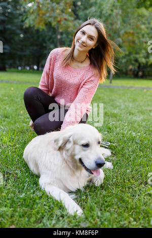 Photo of girl and retriever lying on lawn - Stock Photo
