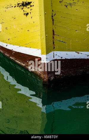 Padstow, Cornwall, South West England, UK 03/12/2017. The Weather Beaten Bow of a Fishing Boat Reflects on the Calm - Stock Photo