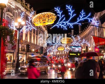 CHRISTMAS SHOPPING SCENE REGENT STREET LIGHTS  LONDON NIGHT Busy scene of Christmas shoppers, blurred traffic and - Stock Photo