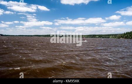 windy Velke Darko pond with wavesm sailboats and blue sky with clouds on Ceskomoravska vrchovina near Zdar nad Sazavou - Stock Photo