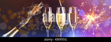 Two full glasses of champagne and one being filled against champagne cork popping - Stock Photo