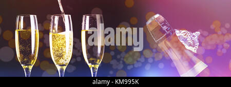 Two full glasses of champagne and one being filled against top of bottle of champagne with ripped foil - Stock Photo