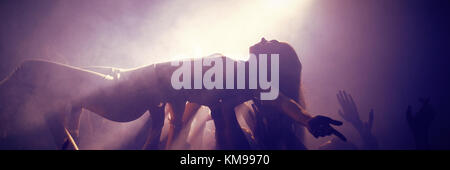Friends lifting woman at concert in illuminated nightclub - Stock Photo