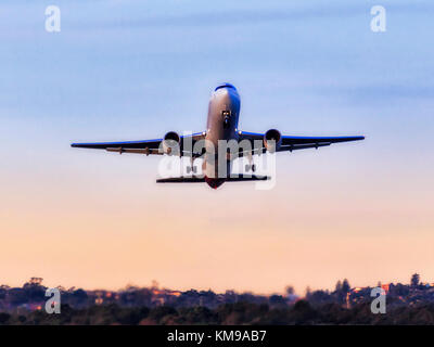 Modern passenger airplane taking off from Sydney International airport against clear blue sky in view of gum trees - Stock Photo