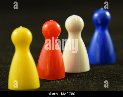 Four colourful Game counters or playing pieces frm a child's game - Stock Photo