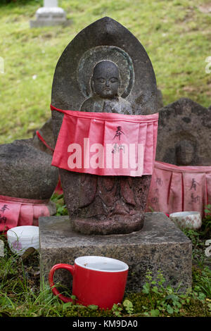 Nara - Japan, May 30, 2017: Traditional stone carved Jizo with red skirt honored and respected with a cup of water - Stock Photo