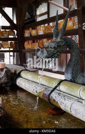 Nara, Japan -  May 30, 2017: A Japanese water dragon at a water pavilion at a Shinto shrine in Nara to purify your - Stock Photo