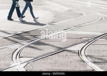 Two people crossing tramlines in the street, Amsterdam, Holland - Stock Photo