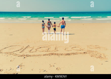 Family on the beach and the Word Ohana written in the sand - Stock Photo