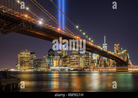 Tribute in Light with the Brooklyn Bridge and the skycrapers of Lower Manhattan. Financial District, New York City - Stock Photo