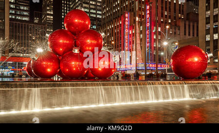 Giant red Christmas ornaments on 6th Avenue with holiday season decorations. Midtown. New York City - Stock Photo