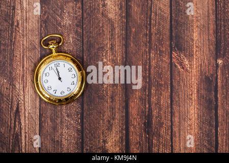 Vintage golden clock showing midnight, on wooden background