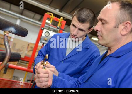 man explaining equipment to trainee - Stock Photo