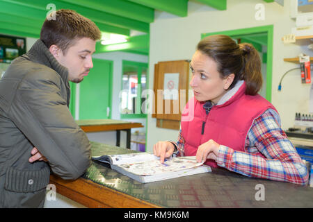 hardware store worker helps entrepreneur client choosing tools and materials - Stock Photo