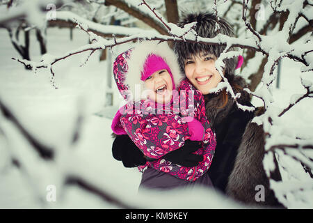 mom with kid spending time in winter park - Stock Photo