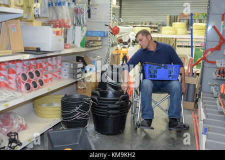 man pushing wheelchair with daughter in shopping-center - Stock Photo