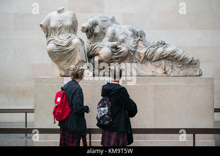 London. England. Visitors to the British Museum looking at the ancient Parthenon sculptures aka Elgin Marbles. - Stock Photo
