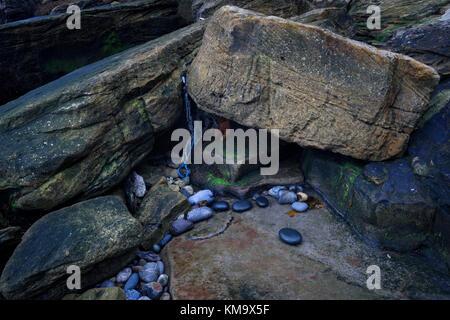 Marine debris washed ashore among coastal rocks  on the Northumberland coast. - Stock Photo