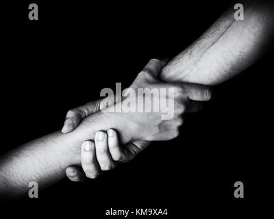 Man saving, rescuing and helping woman by holding or griping the forearm. Male hand and arm pulling up female. Concept - Stock Photo