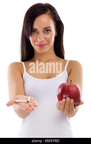 a young woman holding in one hand a broken cigarette in the other healthy apple cigar,stop smoking concept on white - Stock Photo